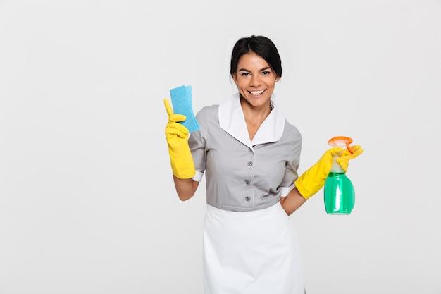 Portret van een vrolijke aantrekkelijke huishoudster