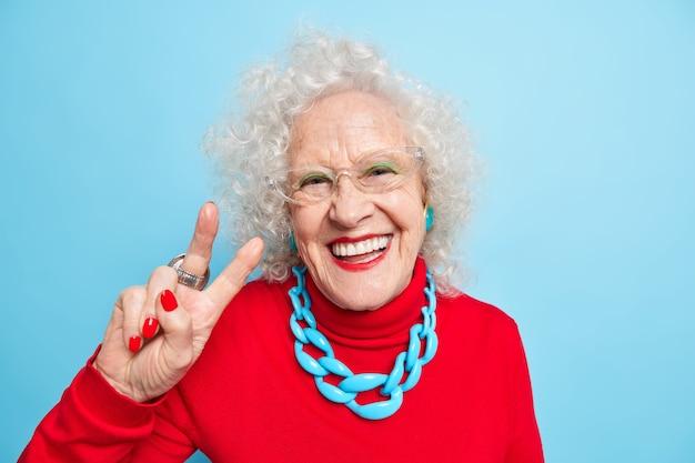 Portret van een vrolijke, aardig uitziende oudere vrouw die lacht en vrolijk een vredesgebaar maakt toont een v-teken gekleed in een rode trui met ketting drukt positieve emoties uit