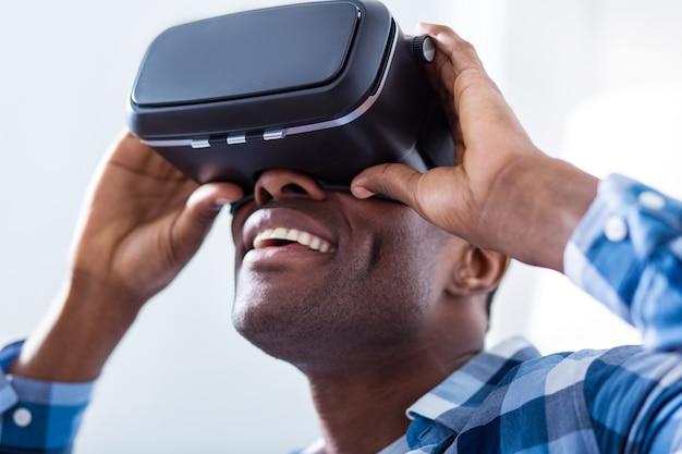 Portret van een vrolijke aardige positieve man die lacht en in een geweldige bui is terwijl hij een 3d-bril draagt