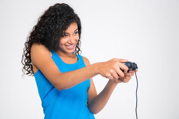 Portret van een vrolijke afro-amerikaanse vrouw die in videogame met joystick speelt die op een witte muur wordt geïsoleerd