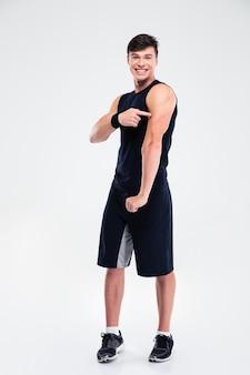 Portret van een vrolijke atletische man die met de vinger naar zijn geïsoleerde spieren wijst