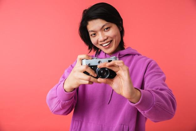 Portret van een vrolijke aziatische man die geïsoleerd over een roze muur staat en een foto maakt met een fotocamera