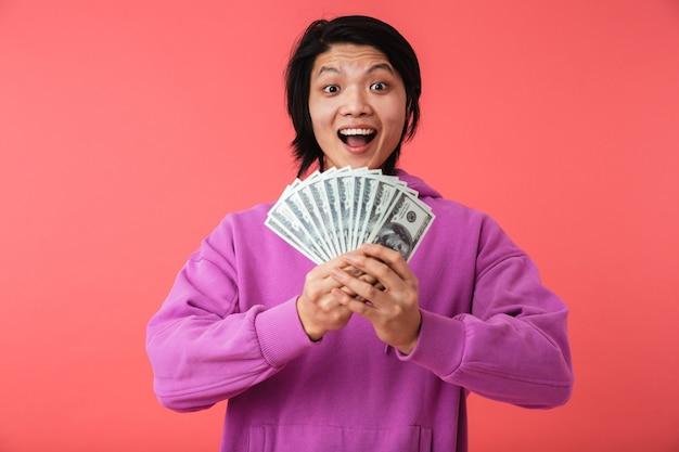 Portret van een vrolijke aziatische man die geïsoleerd over een roze muur staat en geldbankbiljetten toont