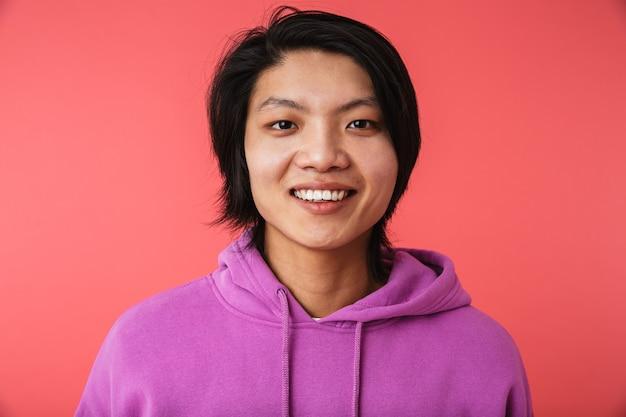 Portret van een vrolijke aziatische man die geïsoleerd over een roze muur staat en naar de camera kijkt