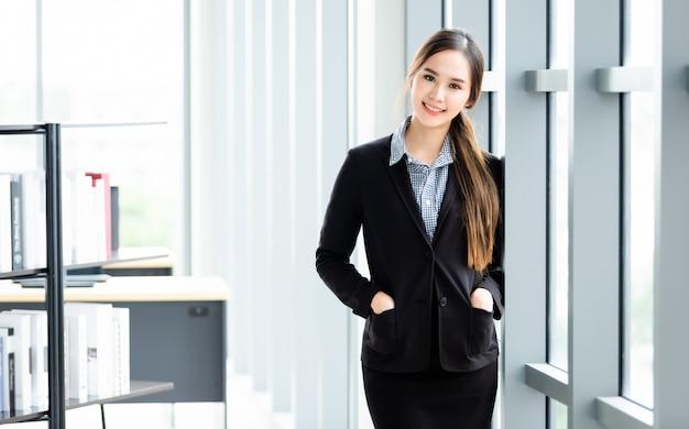 Portret van een vrolijke aziatische onderneemster op het kantoor