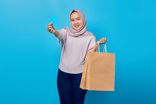 Portret van een vrolijke aziatische vrouw die een boodschappentas vasthoudt en een creditcard toont over een blauwe achtergrond