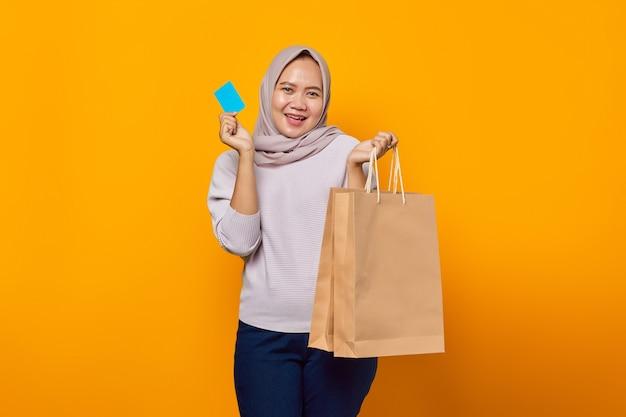 Portret van een vrolijke aziatische vrouw die een boodschappentas vasthoudt en een creditcard toont over een gele achtergrond