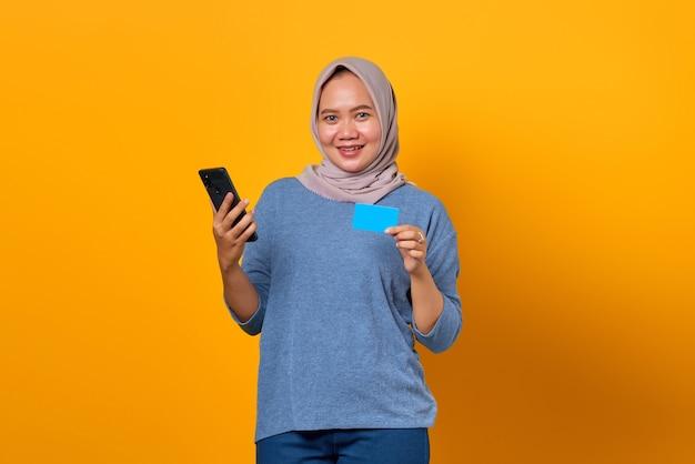Portret van een vrolijke aziatische vrouw die een mobiele telefoon vasthoudt en een creditcard toont over een gele achtergrond