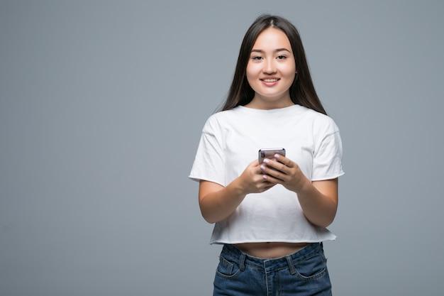 Portret van een vrolijke aziatische vrouw die mobiele telefoon houdt en camera over grijze achtergrond bekijkt
