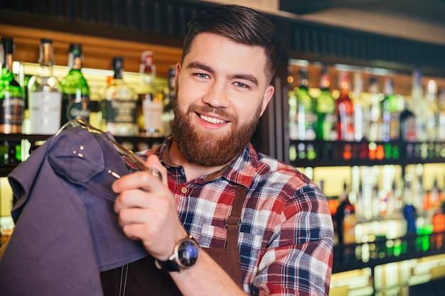 Portret van een vrolijke, bebaarde jonge barman die een bril afveegt in de bar