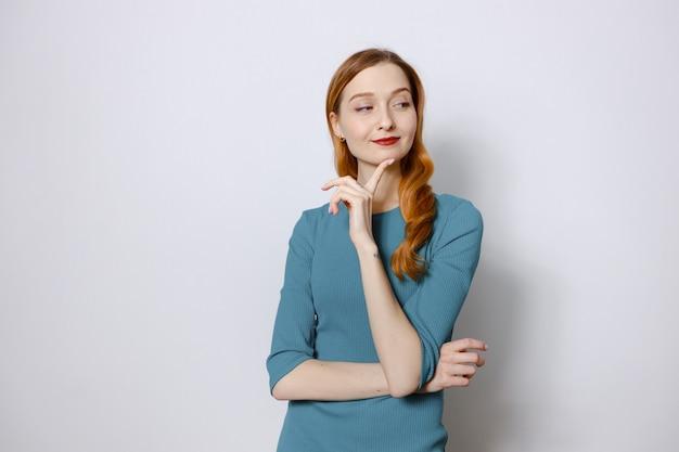 Portret van een vrolijke, bedachtzame roodharige vrouw in een blauwe jurk