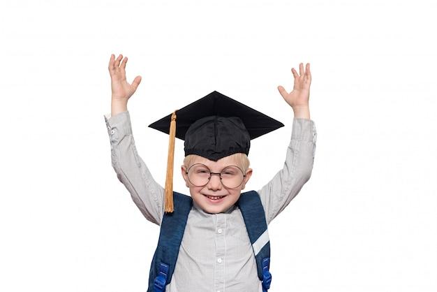 Portret van een vrolijke blonde jongen in grote glazen, academische hoed en een schooltas. handen omhoog. isoleren