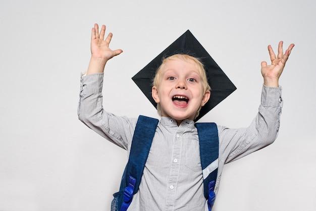 Portret van een vrolijke blonde jongen met academische hoed en een schooltas. handen omhoog. witte achtergrond.