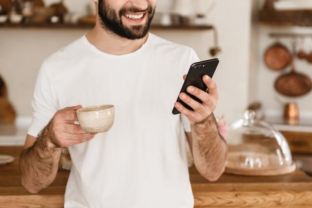 Portret van een vrolijke brunette man die koffie drinkt en smartphone gebruikt terwijl hij thuis ontbijt in een stijlvolle keuken