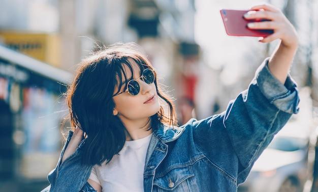 Portret van een vrolijke dame die een selfie maakt terwijl ze door haar zonnebril kijkt en een blauwe jas draagt