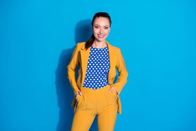 Portret van een vrolijke droom, dromerig, elegant, charmant representatief meisje met een zak met handen ziet er goed uit geïsoleerd over een blauwe kleurachtergrond