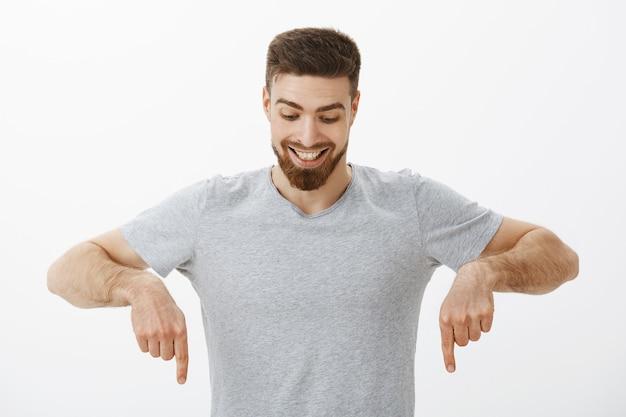 Portret van een vrolijke en verbaasde knappe mannelijke man met perfecte haarstijl en baard die naar beneden kijkt en met vreugde en nieuwsgierigheid naar beneden kijkt, genietend van naar beneden kijken naar interessante kopie ruimte