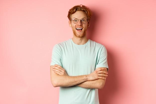 Portret van een vrolijke europese man met een bril die verbaasd naar de camera kijkt, zie interessante promotiestan...