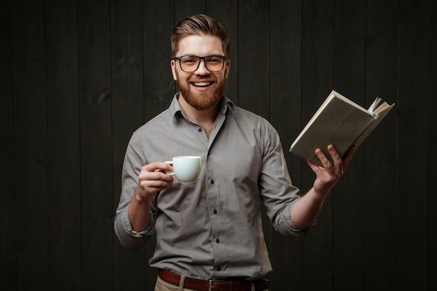 Portret van een vrolijke, gelukkige man in brillen en hemd die een boek leest en een kopje koffie vasthoudt, geïsoleerd op een zwart houten oppervlak