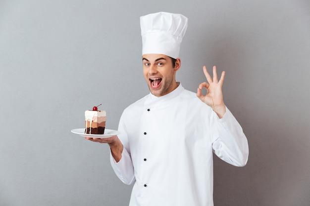 Portret van een vrolijke gelukkige mannelijke chef-kok gekleed in eenvormig
