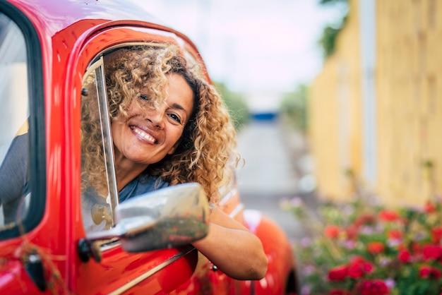 Portret van een vrolijke, gelukkige volwassen mooie vrouw die lacht en geniet van autorijden