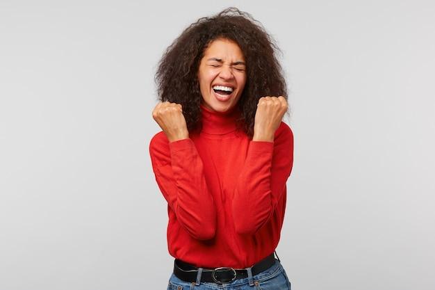 Portret van een vrolijke gelukkige vrouw in rode trui balde vuisten als winnaar met gesloten ogen