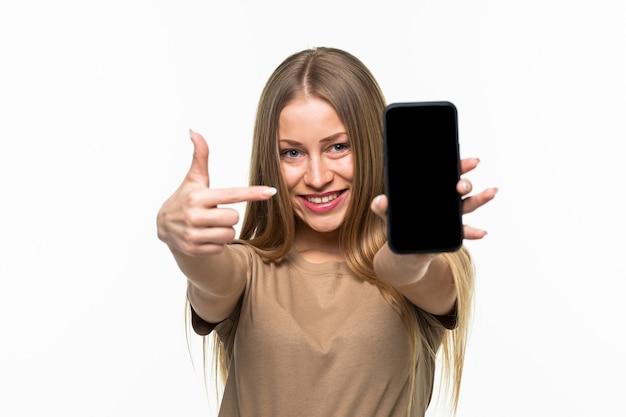 Portret van een vrolijke glimlachende vrouw die met de vinger wijst naar een mobiele telefoon met een leeg scherm