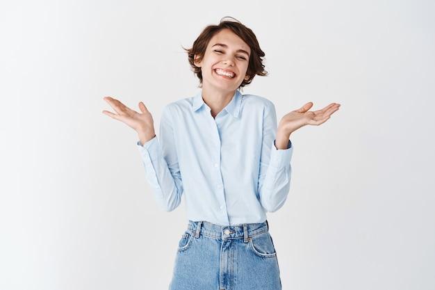 Portret van een vrolijke glimlachende vrouw, schouderophalend en gevleid lachen, geprezen, complimenten ontvangen op de witte muur