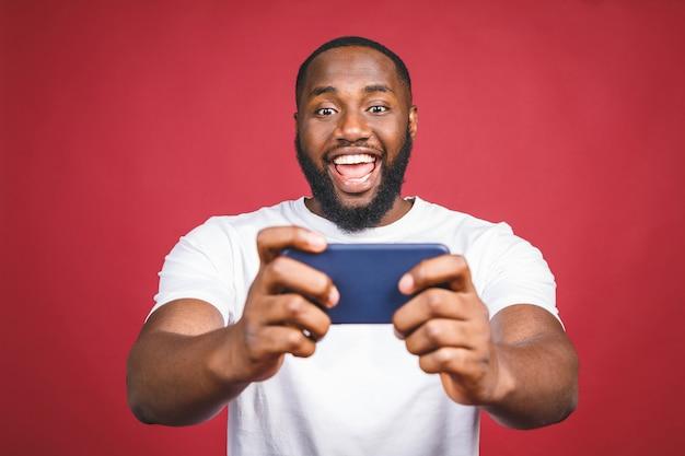 Portret van een vrolijke jonge afrikaanse man gekleed in casual spelletjes spelen op mobiele telefoon geïsoleerd op rode achtergrond.