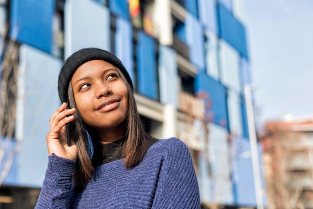 Portret van een vrolijke jonge afrikaanse vrouw die zich in openlucht en een telefoongesprek bevinden terwijl weg het kijken