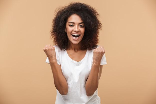 Portret van een vrolijke jonge afrikaanse vrouw vieren