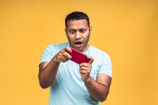 Portret van een vrolijke jonge afrikaanse zwarte indiase man gekleed in casual spelletjes op mobiele telefoon geïsoleerd op gele achtergrond.