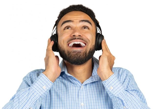 Portret van een vrolijke jonge afro-amerikaanse mens die aan muziek met hoofdtelefoons luistert