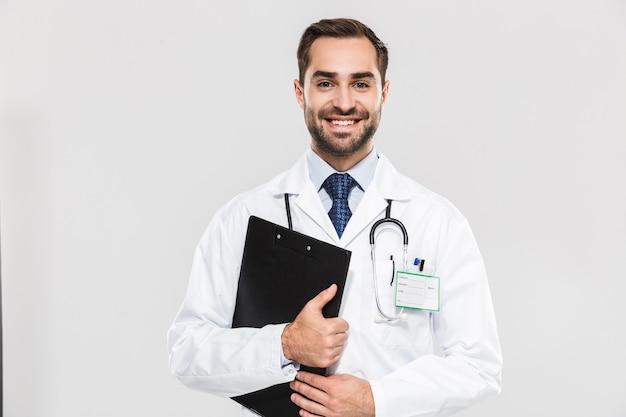 Portret van een vrolijke jonge arts die lacht en een gezondheidskaart vasthoudt die over een witte muur wordt geïsoleerd
