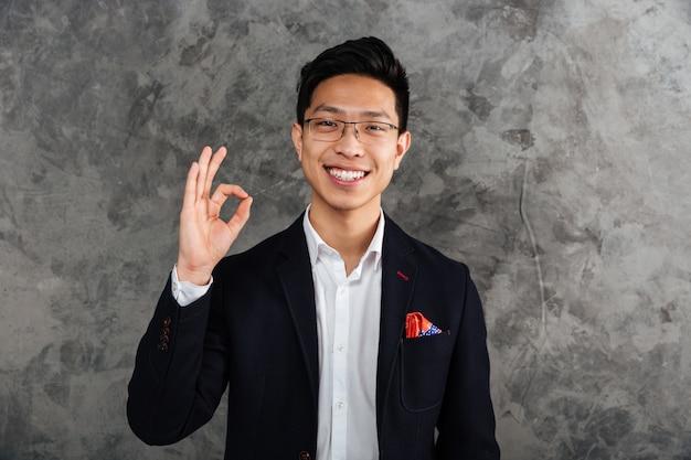 Portret van een vrolijke jonge aziatische man gekleed in pak