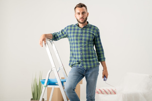 Portret van een vrolijke jonge, bebaarde man die met een verfroller op een trapladder staat in een nieuw appartement met bewegende spullen