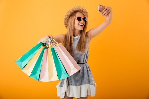Portret van een vrolijke jonge blonde vrouw in zomerhoed