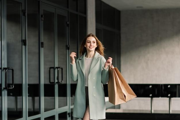 Portret van een vrolijke jonge dame met boodschappentassen buiten