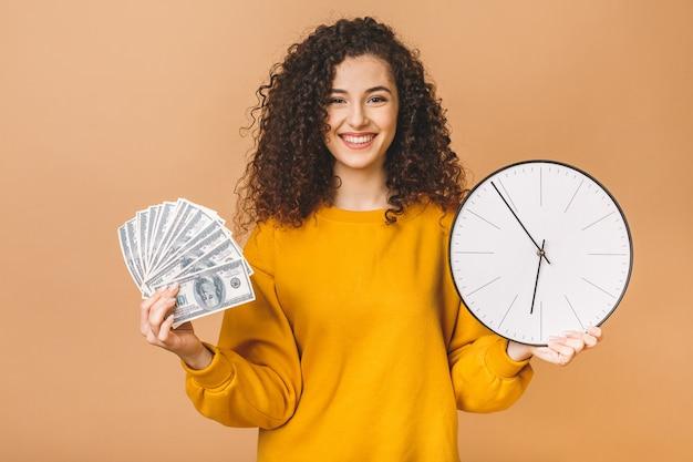 Portret van een vrolijke jonge het geldbankbiljetten en klok van de vrouwenholding, vieren geïsoleerd over beige achtergrond.