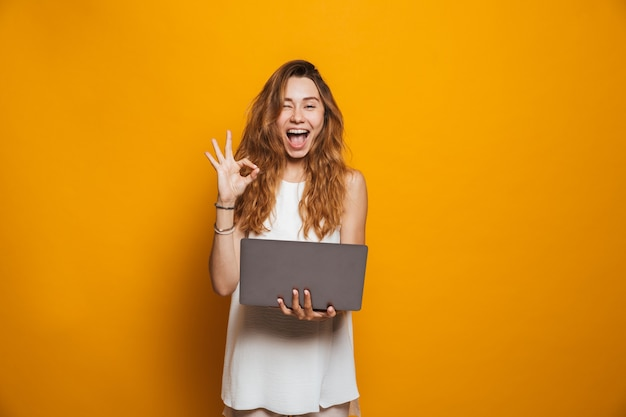 Portret van een vrolijke jonge laptop van de meisjesholding