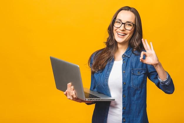 Portret van een vrolijke jonge laptop van de vrouwenholding en ok tonen