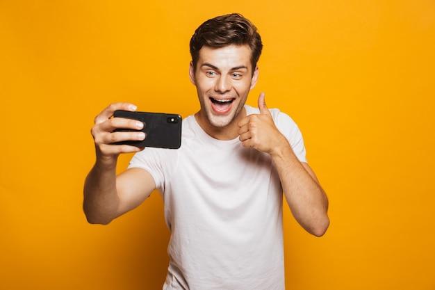 Portret van een vrolijke jonge man die een selfie neemt