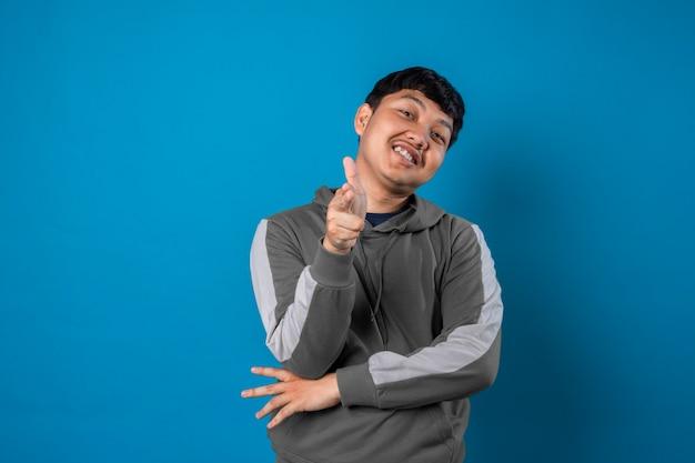 Portret van een vrolijke jonge man die een wijzend gebaar toont dat op de blauwe achtergrond wordt geïsoleerd