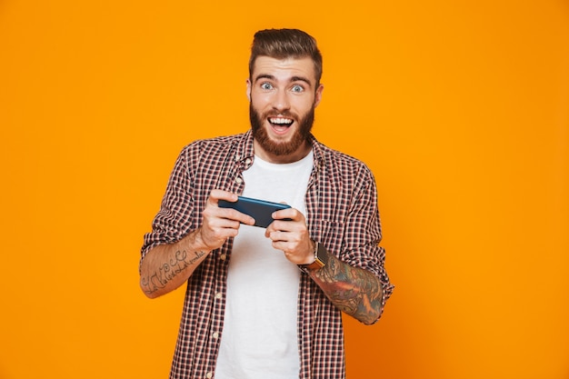 Portret van een vrolijke jonge man die vrijetijdskleding draagt die spelletjes speelt op de mobiele telefoon