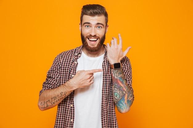 Portret van een vrolijke jonge man die vrijetijdskleding draagt die zijn slimme horloge controleert