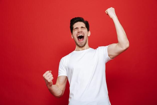 Portret van een vrolijke jonge man in wit t-shirt vieren