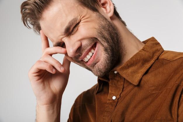 Portret van een vrolijke jonge man met een bruin shirt die aan de voorkant poseert en glimlacht, geïsoleerd over een witte muur