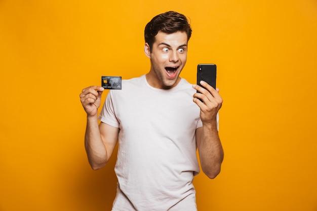 Portret van een vrolijke jonge man met mobiele telefoon