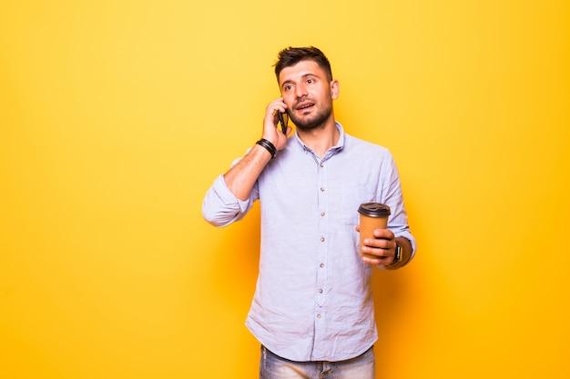 Portret van een vrolijke jonge man met vrijetijdskleding geïsoleerd op gele achtergrond, met afhaalmaaltijden koffiekopje, praten over de mobiele telefoon