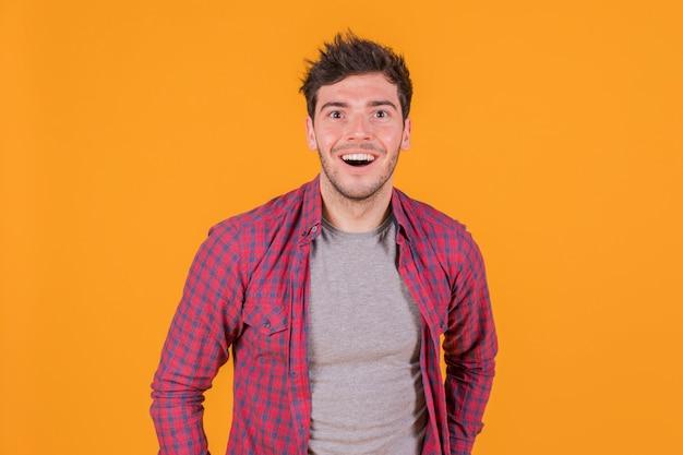 Portret van een vrolijke jonge man tegen een oranje achtergrond